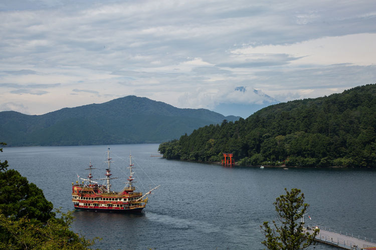Lake Ash in Hakone Lake Ashi Beauty In Nature Cloud - Sky Day Hakone Mountain Mountain Range Nature Nautical Vessel No People Outdoors Pirate Ship River Scenics Sky Transportation Tree Water