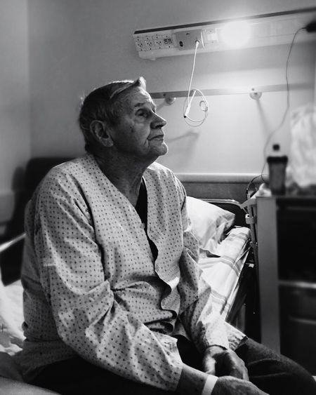 Senior Man Sitting On Bed At Hospital