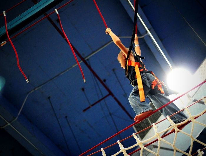Low angle view of boy hanging from ropes