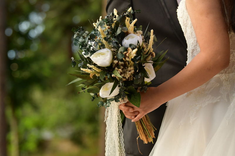 Low angle view of woman holding bouquet of flowering plant