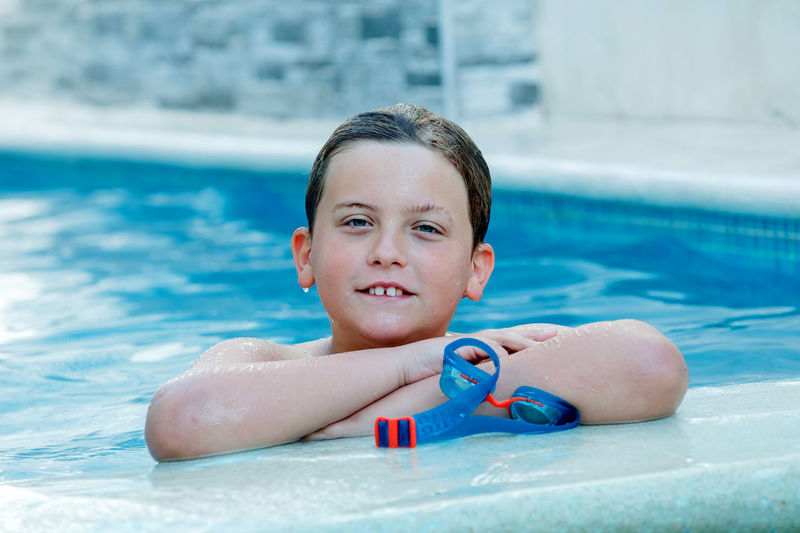 Portrait of boy smiling in swimming pool