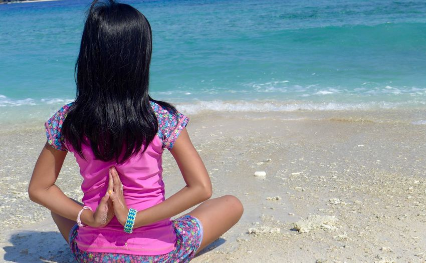Rear View Of Girl Doing Yoga At Beach