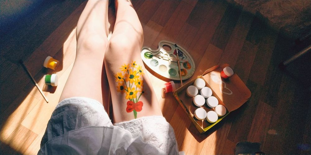Midsection of woman with painted thigh at home