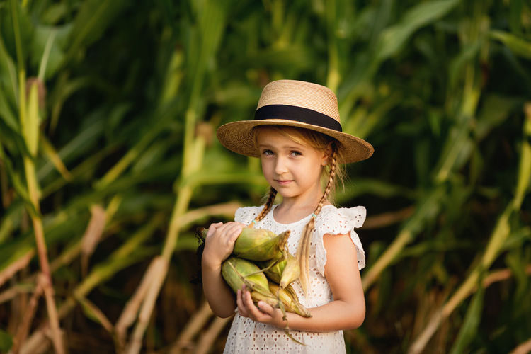 Portrait of cute girl holding corn standing outdoors