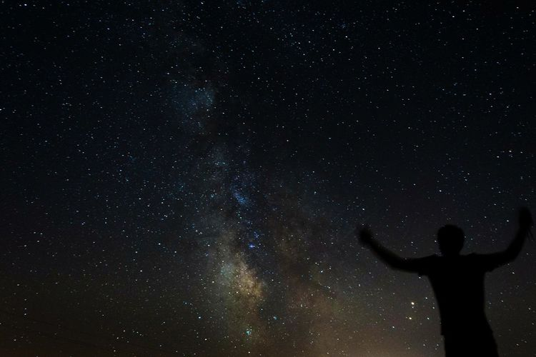 Silhouette person standing against star field at night