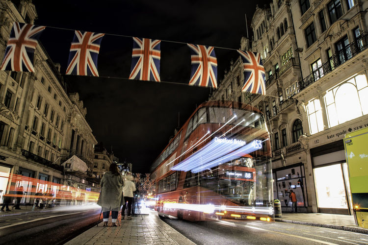 Women By Blurred Motion Of Bus With British Flags Hanging In City At Night