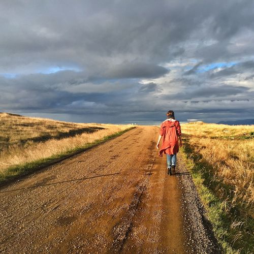 Rear View Of Young Woman Walking Along Dirt Road In Green Field Against Cloudy Sky