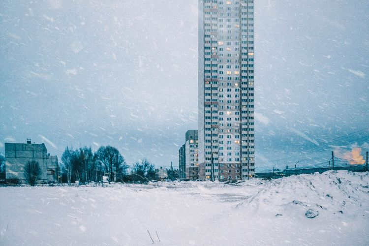 Snow covered buildings against sky