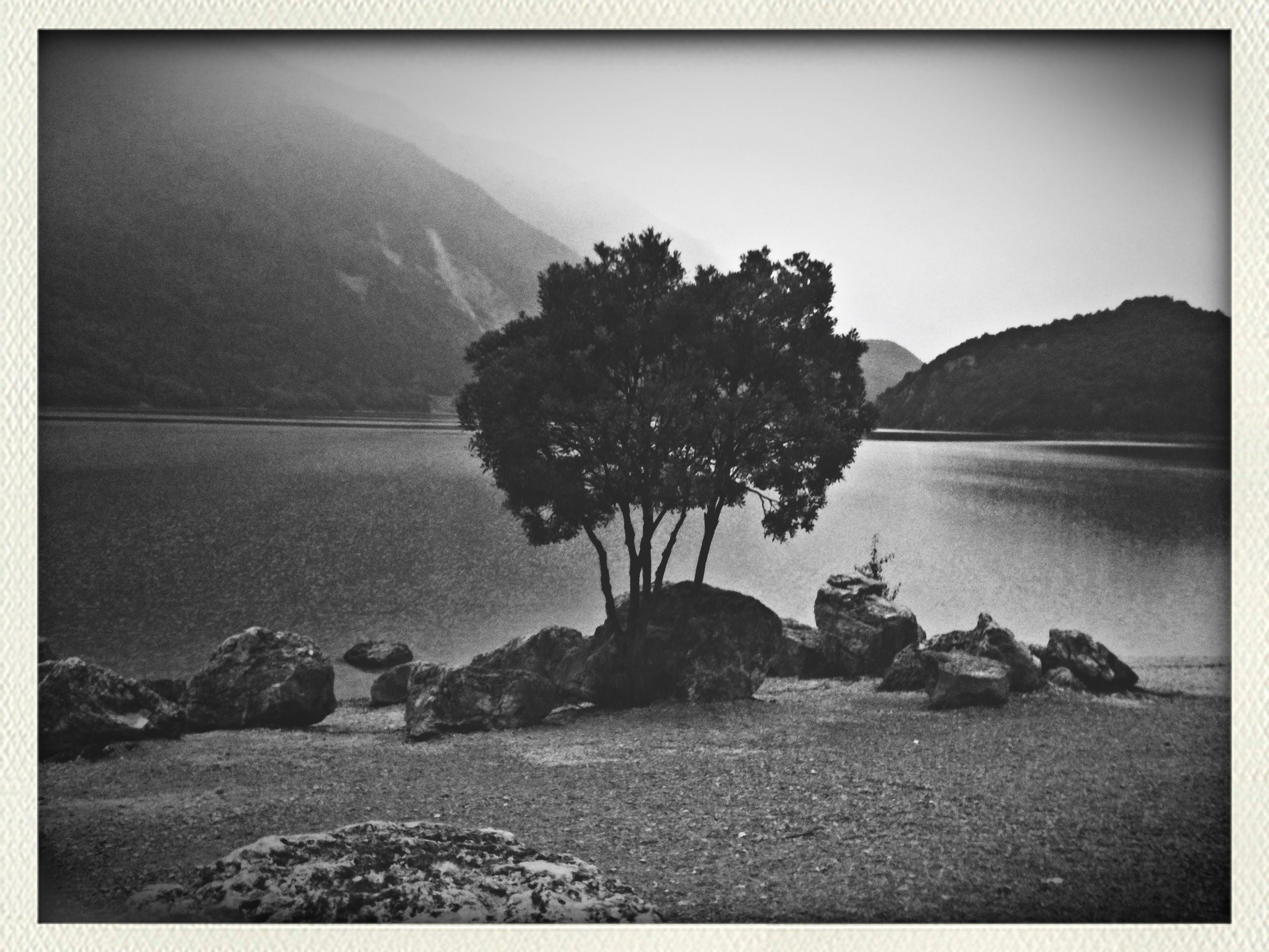 transfer print, water, auto post production filter, tranquility, tranquil scene, scenics, clear sky, tree, sea, nature, beauty in nature, rock - object, sky, mountain, reflection, beach, shore, silhouette, lake, idyllic