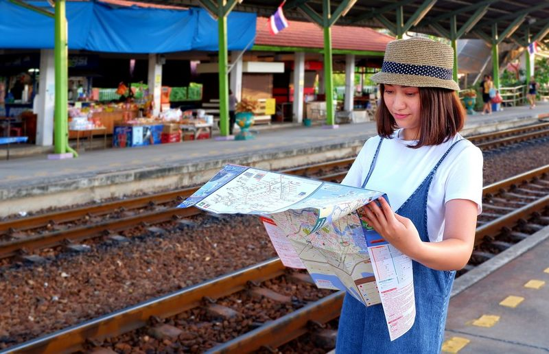Young female traveler in casual style with hat looking map on railway platform at train station during travel on train, lifestyle in travel concept Map Travel Traveler Train Station Railway Railroad Track Casual Lifestyle Outdoors Asian  ASIA Journey Bamboo Hat Vintage Style Smiling Blurred Background Looking City Urban EyeEm Selects Beautiful Woman Women Beautiful People Portrait Young Women Females Public Transportation Railroad Platform Rail Transportation Tourism