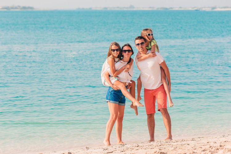 Full length portrait of friends standing on beach