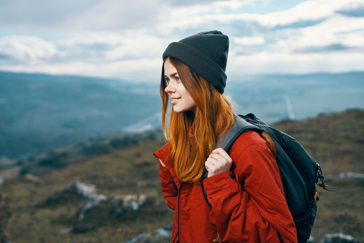 Woman wearing hat standing against mountain during winter