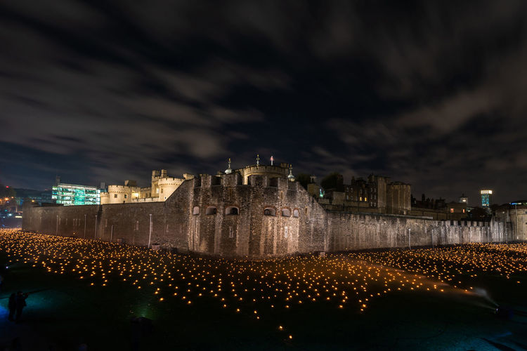 LONDON, UK - NOVEMBER 06, 2018: The Tower of London's moat has been filled with around 10,000 lit torches to mark the centenary of the end of the First World War. Illuminated Architecture Building Exterior Built Structure Night Sky Cloud - Sky City Building Reflection Outdoors Group Of People History Travel Destinations The Past Cityscape Light London Tower Of London Moat Armistice Rememberance Day First World War Dusk Torches