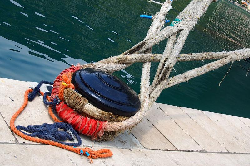 Ropes tied up on bollard at harbor