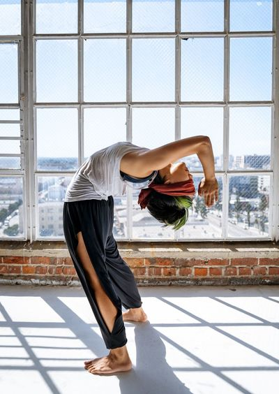 Side view of woman exercising against window