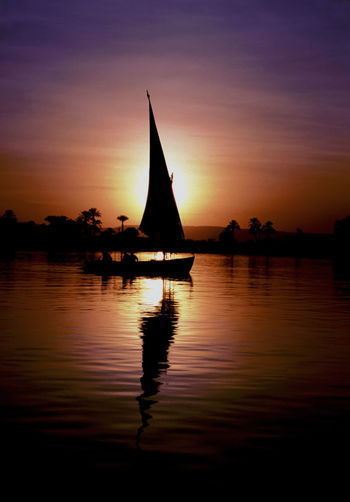 Feluca on the Nile at sunset Feluka Nile River Holiday Evening Sunset Reflection Full Sail Water Nautical Vessel Sunset Astronomy Sailboat Silhouette Saturated Color Reflection Romantic Sky Dramatic Sky Atmospheric Mood Atmosphere Moody Sky Mast