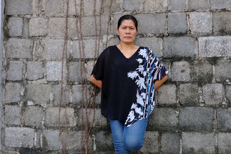 Mature woman wearing casuals while standing against wall