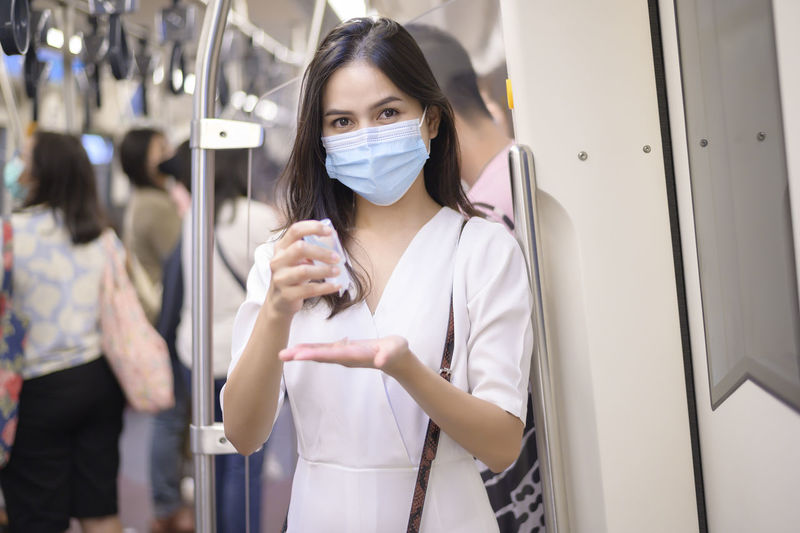 Portrait of woman using hand sanitizer at train