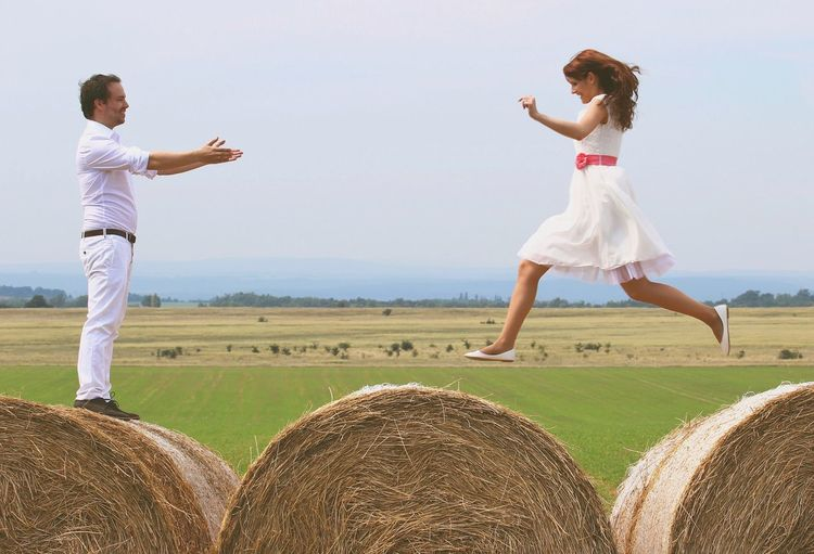 Woman Jumping On Hay Bales Towards Embracing Man