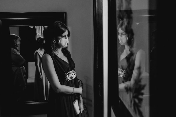 Bride wearing mask standing by mirror