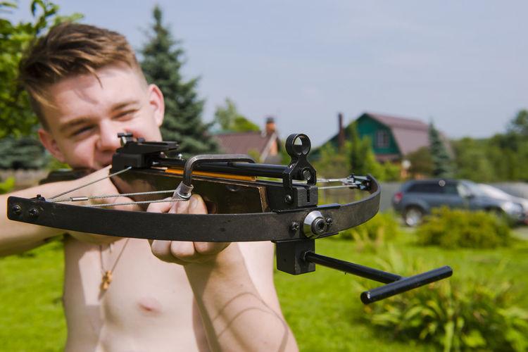 Shirtless Man Using Cross Bow At Yard
