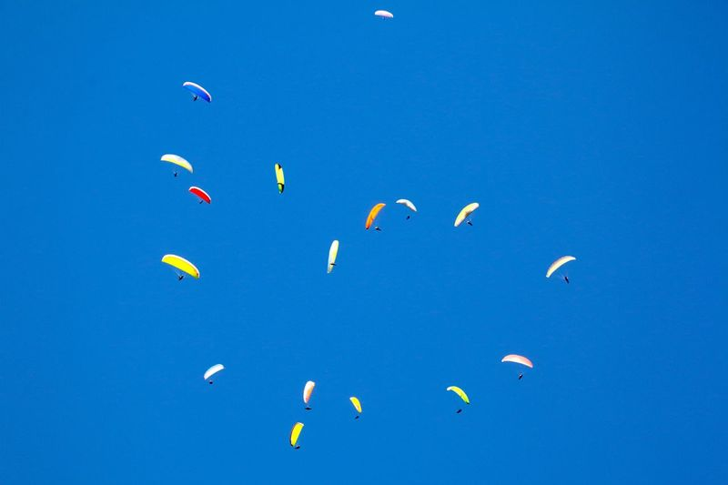 Low Angle View Of People Paragliding In Clear Blue Sky