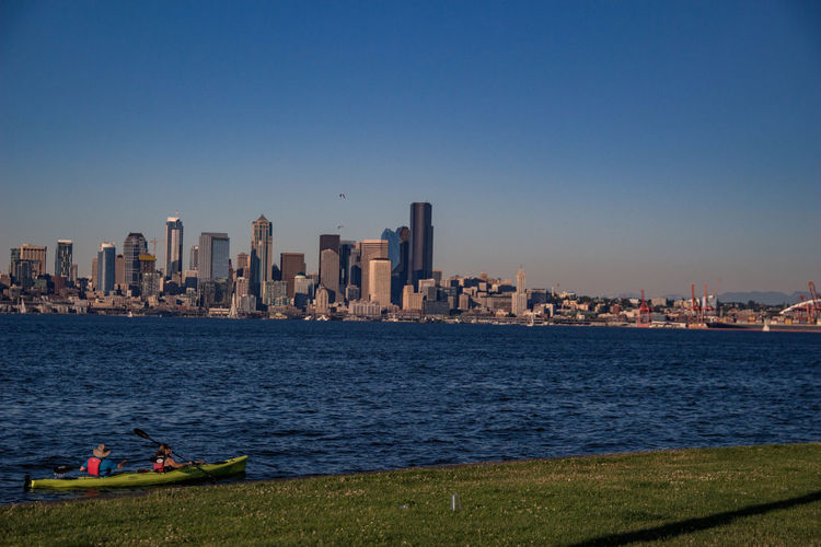 Cityscape by sea against clear blue sky