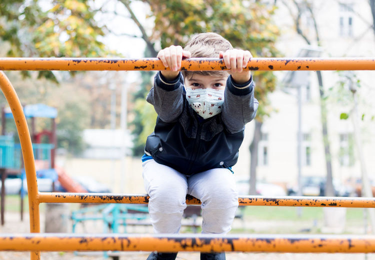 Happy kid playing on the playground and wearing face mask due to covid-19 pandemic.