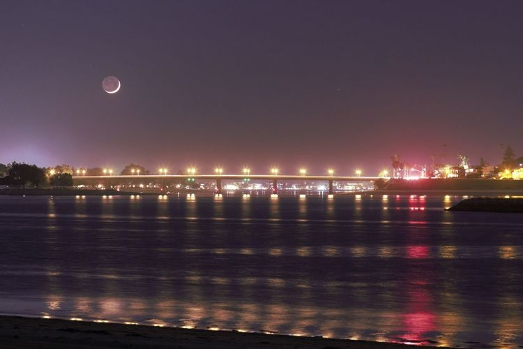 """A few nights ago while driving around Fiesta Island, I spotted the moon over a bridge. So I stopped and took a quick snap of it. I take photos of anything I see, and I always use """"manual mode"""". I learned to use my camera on my own without any knowledge of it. If you love something, you just keep playing with it even if the outcome does not look right at all. You don't even feel any failures. You just get back up and try another way to just make it happen. Just keep trying and trying and keep trying different ingredients (exposure length, ISO, aperture, etc) and mixtures until you are satisfied enough on what you create. Gladly, cameras are not heavy so it doesn't really take a lot of muscle to learn it. Imagine if it was a heavy equipment. I'm sure I'd give up a lot sooner. This photo is directly from my other girlfriend, my Canon SL1. Hehe. I wish I knew how to use lightroom and/or photoshop. I'm sure I can create something awesome and I'm sure you can as well. I love taking photos. Bridges California Fiesta Island, San Diego, CA Mission Bay Park Moon Over Bridge Moon Over Water At Night Night Photography No Edits No Filters Reflections On The Water San Diego After Sunset Beauty In Nature Colorful Reflections Illuminate Canon_5D_MarkII Scenics 2017 Manual Mode Photography Moonlight Nightscape October 2016 Be. Ready. Colour Your Horizn California Dreamin"""