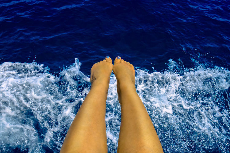 Low Section Of Woman Legs Over Sea