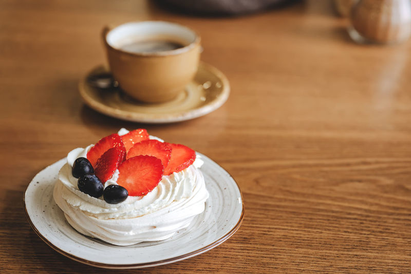 Coffee cup and cake on table