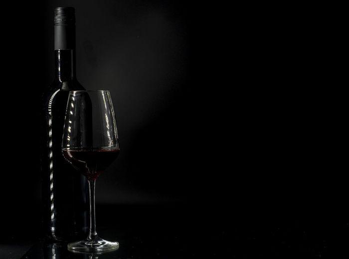 Glass of wine bottles against black background