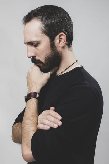 bearded thoughtful man on gray background Contemplation Standing Young Men White Background Young Adult Facial Hair Beard Indoors  One Person Studio Shot Indoors  Casual Clothing Waist Up Wall - Building Feature Looking Gray Gray Background Black Color Men Front View