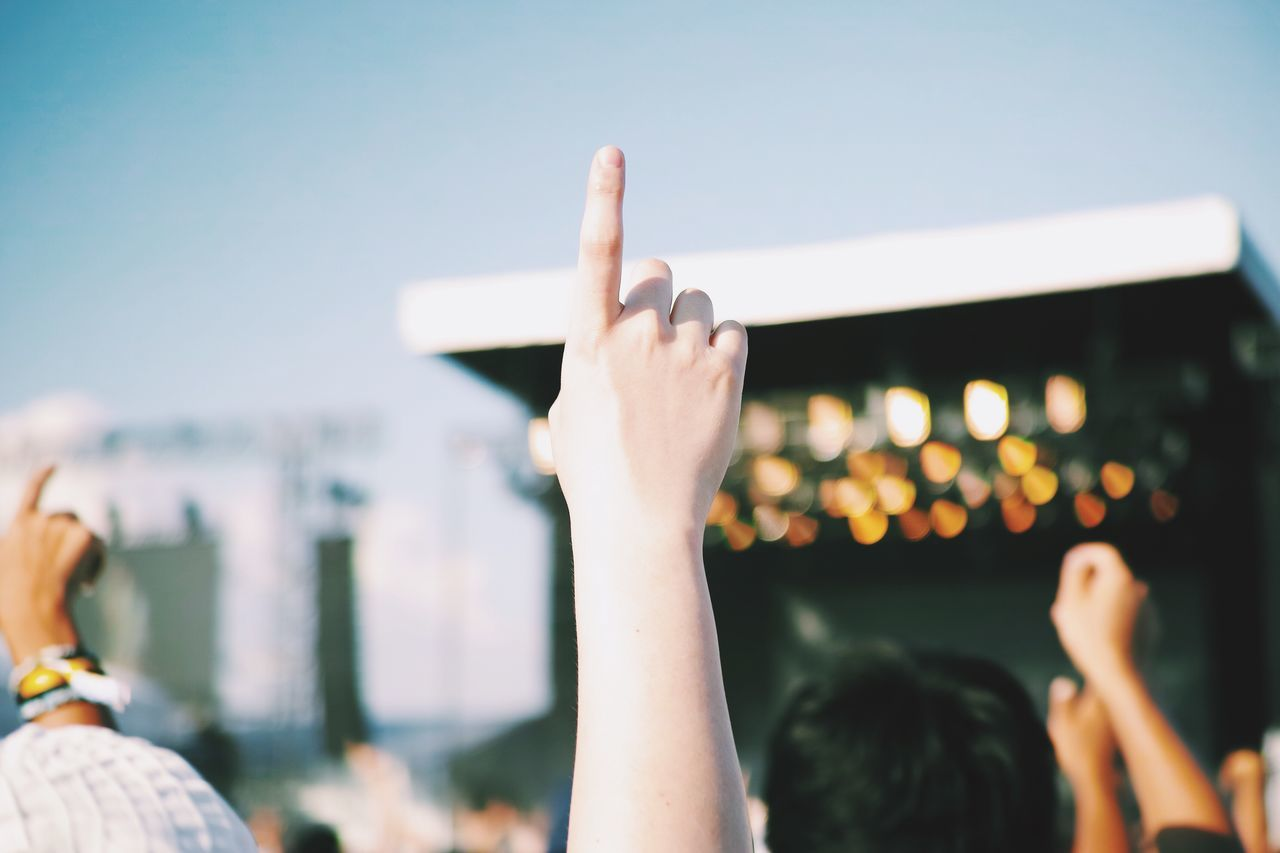 Cropped image of people pointing towards sky in music concert