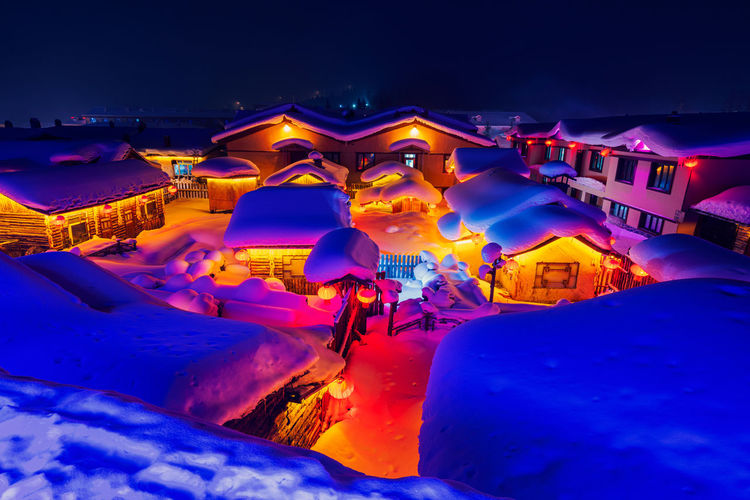 People in snow against blue sky at night