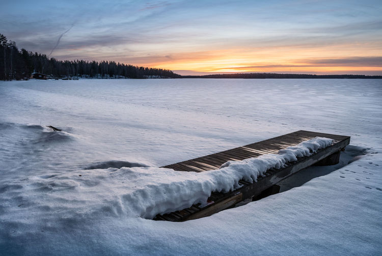 Scenic winter landscape with pier and sunset at evening light in Finland Cold Temperature Winter Water Sky Sunset Snow Scenics - Nature Beauty In Nature Nature Frozen No People Ice Tranquility Cloud - Sky Tranquil Scene White Color Non-urban Scene Lake Outdoors Cold Finland Landscape Tranquility Pier Peaceful