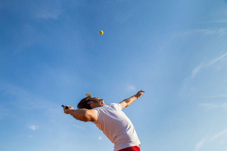 Professional tennis player throwing ball in the air before hitting it. Adult Athlete Athletic Court Lifestyle Active Activity Air Ball Competition Fit Healthy Hit Joy Match person Player Professional Racket Sky Sport Sportwear Tennis 🎾 Throw Training