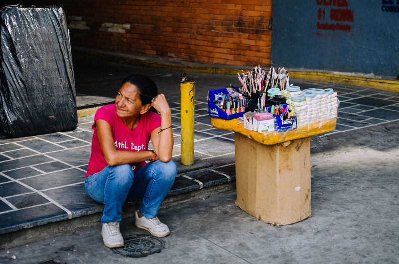 Earning the life The Art Of Street Photography Sitting Full Length Casual Clothing Front View Emotion Real People One Person Women Smiling Adult Lifestyles Leisure Activity Looking At Camera Architecture Day Portrait Females Happiness Mid Adult Jeans Hairstyle Streetphotography Street Photography EyeEm EyeEm Best Shots EyeEm Selects The Street Photographer - 2019 EyeEm Awards