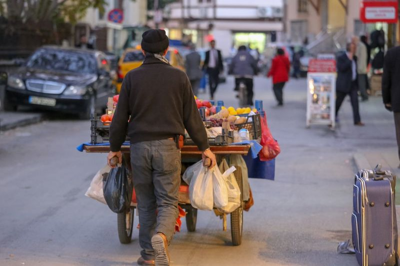Turkish Street Vendor pushing his cart Food And Drink For Sale Street Vendor EyeEm Selects City Street Rear View Real People Transportation Incidental People Walking Architecture Focus On Foreground Road Mode Of Transportation People Men Lifestyles Adult Day City Life Outdoors