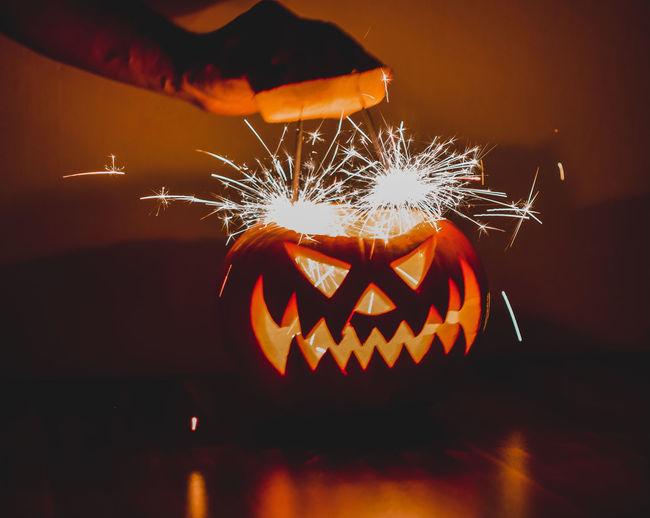 Close-up of illuminated hand holding pumpkin