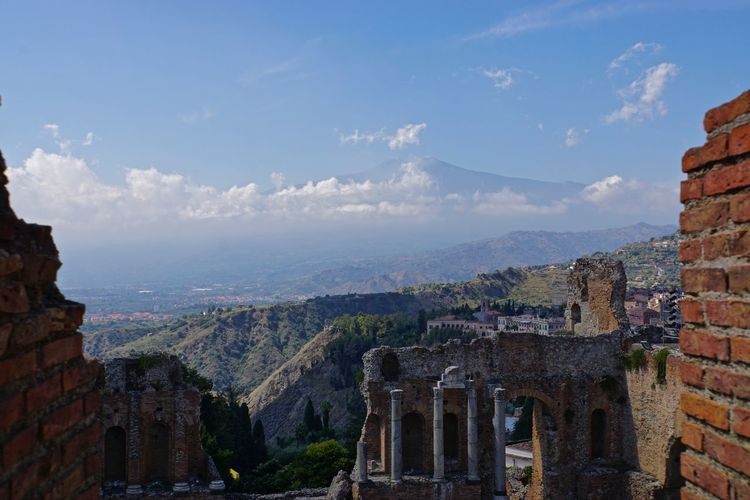 Scenic view of mt etna against sky seen from old ruins in city