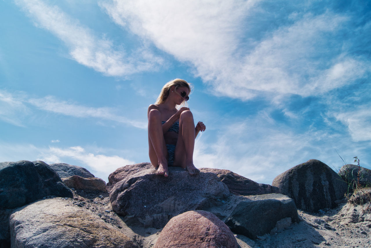 LOW ANGLE VIEW OF MAN SITTING ON ROCK