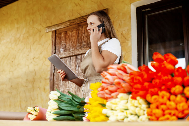 A young female florist with a tablet in her hands is talking on the phone and making an order