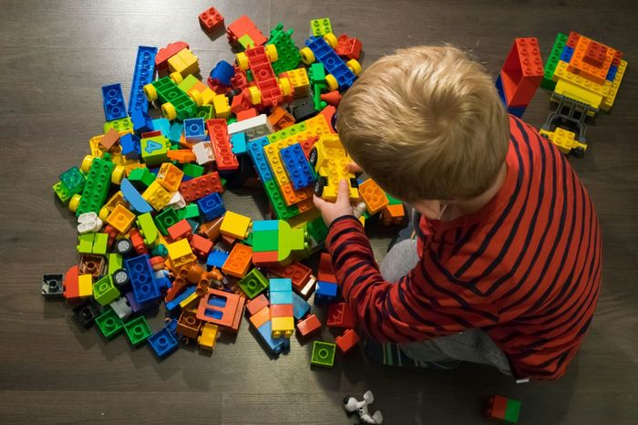 Boy Overhead Above Top Playing LEGO Duplo Toys Bricks Multicoloured Child Childhood Creativity Creative Pile Colourful Blonde Hair Son Toddler  Behind Back Looking Building Creating