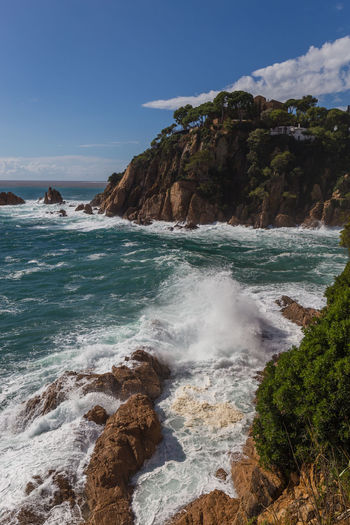 Rocky coastline and crashing waves of the Costa Brava, Spain, against blue sky Water Sea Beauty In Nature Rock Sky Scenics - Nature Motion Solid Rock - Object Beach Wave Nature No People Outdoors Rocky Coastline SPAIN Costa Brava Barcelona Tossa De Mar Land Rock Formation Aquatic Sport Power In Nature