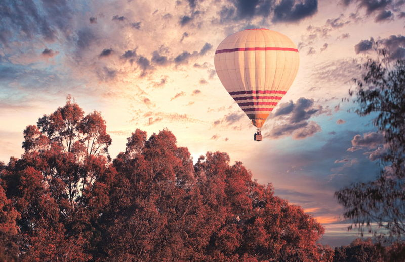 Digital composite image of hot air balloons against sky during sunset