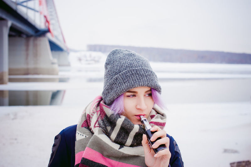 Vaping Childhood Close-up Cold Temperature Day Focus On Foreground Front View Knit Hat Leisure Activity Lifestyles Nature One Person Outdoors Real People Scarf Snow Vape Warm Clothing Winter Young Adult Young Women