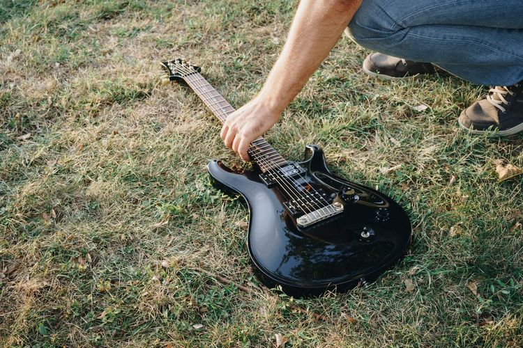 Low Section Of Man Picking Up Electric Guitar On Grassy Field