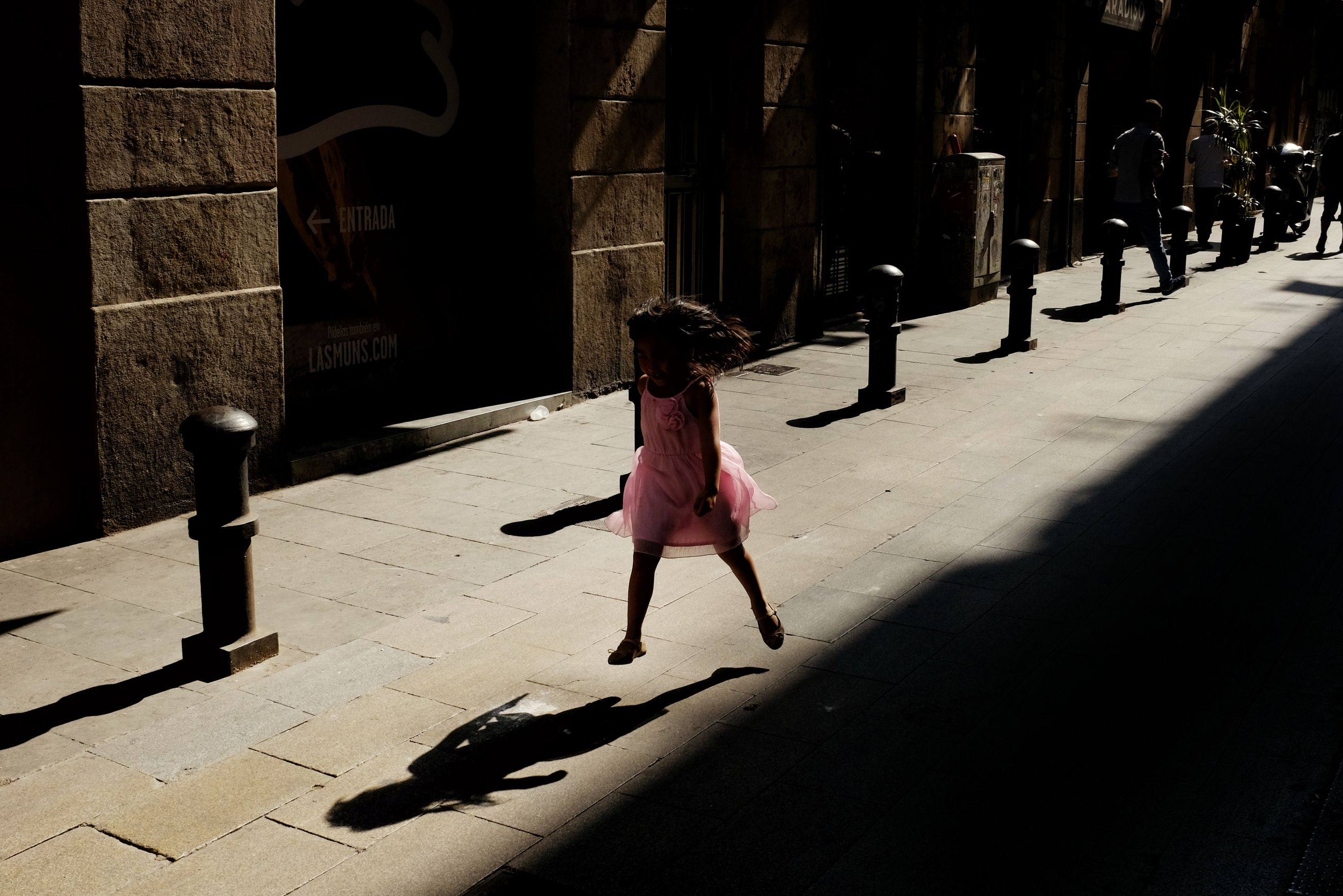 real people, one person, full length, built structure, architecture, walking, shadow, sunlight, outdoors, rear view, day, leisure activity, women, lifestyles, architectural column, building exterior, city, adult, people