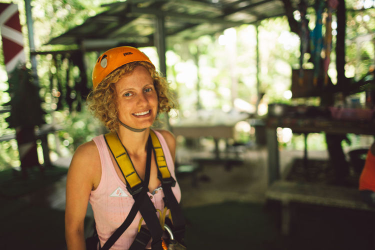 Portrait of smiling woman wearing safety harness with headwear outdoors